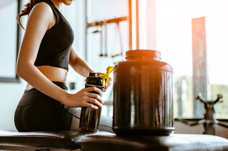 Relaxing after training.beautiful young woman looking away while sitting  at gym.young female at gym taking a break from workout.woman brewing protein shake. Stock Photo