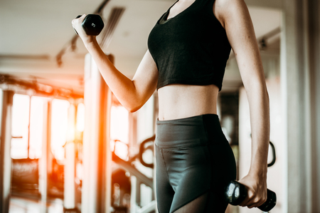 Young woman training with dumbbell in gym.exercising concept.fitness and healthy lifestyle