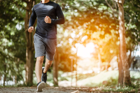 young man running in the nature. Healthy lifestyle.Active healthy runner jogging outdoor.Young Man Running In Wooded Forest Area