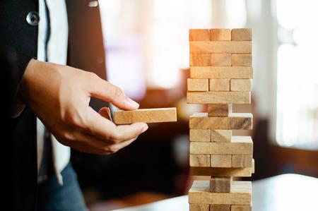 Mano de hombre de negocios sacando o colocando un bloque de madera en la torre de la oficina moderna. plan y estrategia en los negocios. desenfoque de fondo.