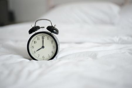 Alarm clock in bed in the morning.