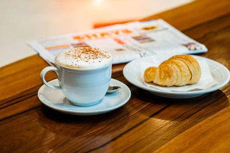 Tasse Cappuccino mit Zeitung auf dem Tisch