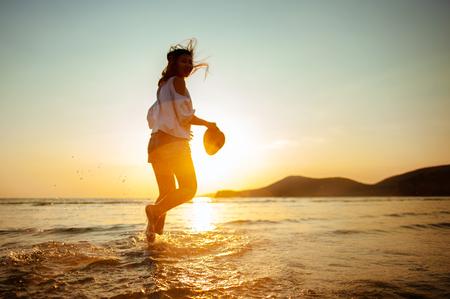 Frau genießt schönen Sonnenuntergang am Strand