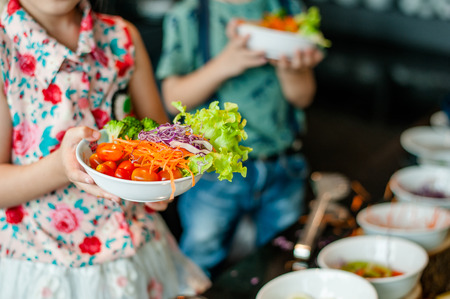 Child taking salad from bowl.