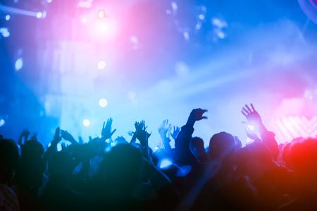 siluetas de mano en concierto. Luz desde el escenario.
