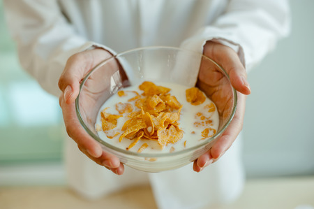 Close Up of Woman' hand holds bowl of cornflakes and milk. Morning concept.Wake up early.Fresh morning