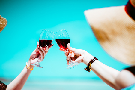 People holding glasses of red wine .wine at a relax party celebration gathering at the beach.Sumer.wine beach two girl.Minimal Summer holidays. Stock Photo