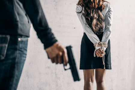 woman hands bound and man holding a gun. Women were handcuffed.woman tied hand.Crime Concept.Criminality Concept. Stock Photo