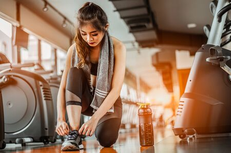woman tying shoe laces.Female sport fitness getting ready for workout in gym. 스톡 콘텐츠