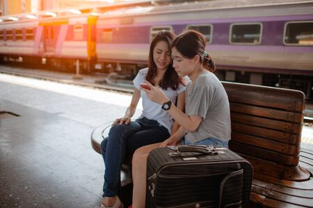 Tourists travelers use smart phone in a train station 스톡 콘텐츠