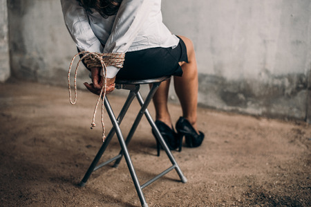 woman hands bound. Women were handcuffed and Sitting on a chair.woman tied hand to a chair.Crime Concept.Criminality Concept. Bonded business. Stock Photo