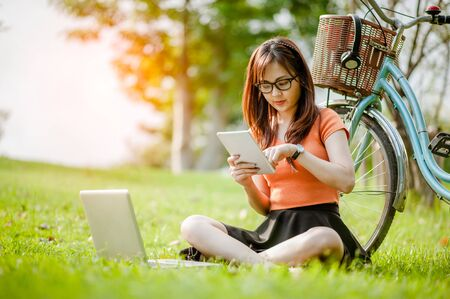 Young beautiful Asian woman working with laptop/internet/online shopping at outdoor park.