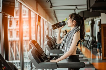 Young woman at treadmill drinking water.Young woman at treadmill drinking .protein shake.