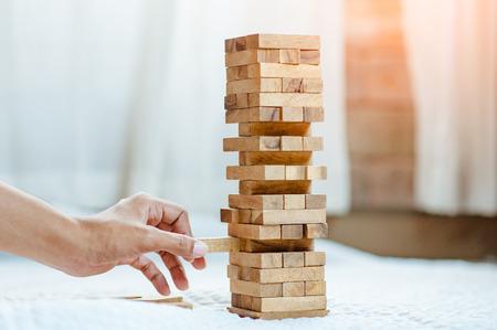 Mano sacando o colocando un bloque de madera en la torre de la oficina moderna. plan y estrategia en los negocios. desenfoque de fondo. Foto de archivo