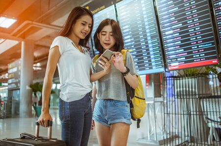Two Women are using their smartphones to Flight Checking at airports.airports and technology concept 스톡 콘텐츠