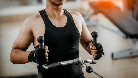 jeune homme faisant une rangée de poulies à câble bas assis. Concept de mode de vie sain. bodybuilder dans la salle de gym.