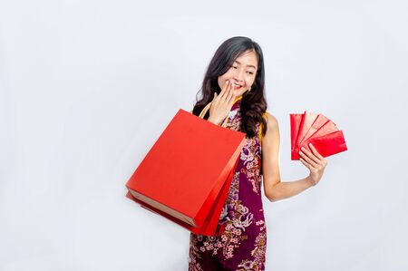 woman wear cheongsam and Carrying a shopping bag in chinese new year.
