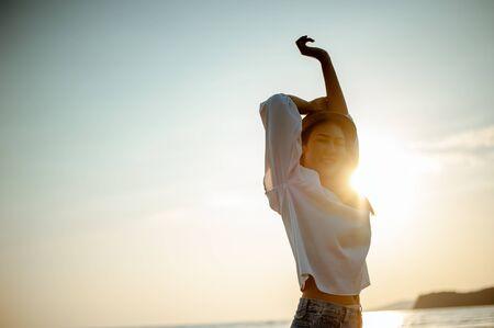 Woman Enjoying Beautiful Sunset on the Beach 스톡 콘텐츠