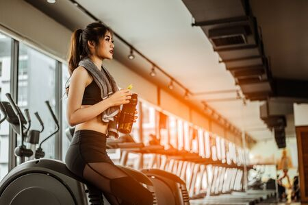 young fitness woman tired in gym drink   protein shake.exercising concept.fitness and healthy lifestyle