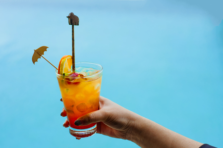 Woman holds a cocktail on swimming pool background.fresh tropical juice cocktail served pool side in Belize.