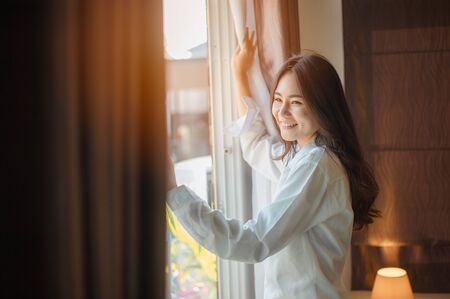 Asian woman wake up in the morning, sitting on white bed and stretching, feeling happy and fresh 스톡 콘텐츠