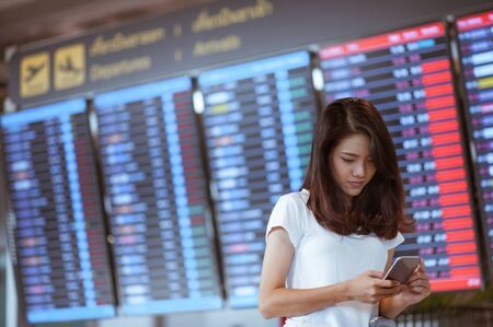 woman in international airport using her mobile phone near the flight information board, 스톡 콘텐츠