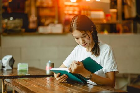 Young woman in a restaurant reading a book.girl sitting by wooden table and reading book 스톡 콘텐츠