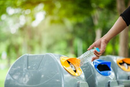 Close up hand throwing empty plastic bottle into the bin. Stok Fotoğraf