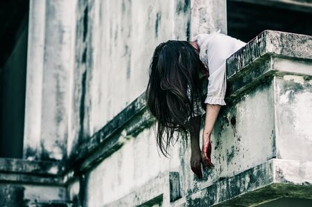 Horror Scene of a Woman with Bloody body.Zombie woman  sitting hanging legs on building is screaming darkness and nightmare horror of scary fear on hell is  devil girl in halloween festival concept