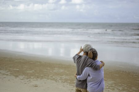 A senior couple hugged each other at the beach in the morning. The old man pointed the finger to the old woman to look at the bright blue sky, life insurance plan at the retirement concept.