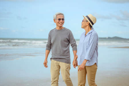 Senior lovers walk hand in hand at the beach at sunrise, plan life insurance at retirement concept. 스톡 콘텐츠