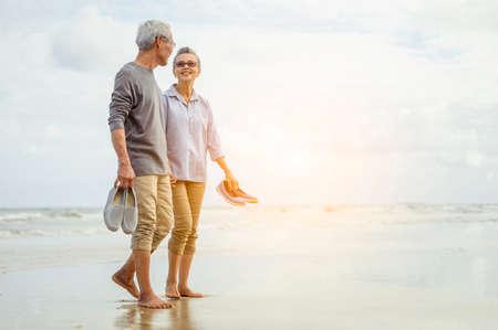 Senior couple walking on the beach holding hands at sunset, plan life insurance at retirement concept. 免版税图像