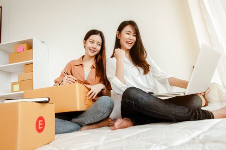 Young woman asian work from home talking with customers to sell products online and delivery for customer. Business owner, SME, shipping, work from home(WFH), freelance, Start up concept. 스톡 콘텐츠