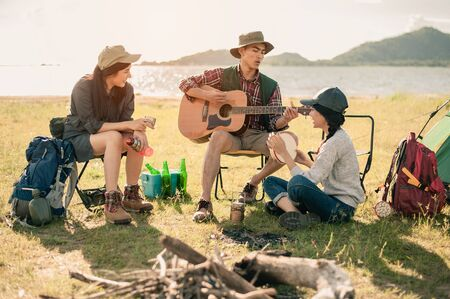 group of young people enjoy in music of drums and guitar on camping trip.