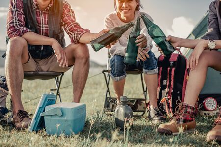 group of tourists clinking beer bottles in camping.adventure, travel, tourism, friendship and people concept.