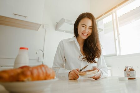 Young woman asia wake up refreshed in the morning and relaxing eat coffee, cornflakes, bread and apple for breakfast at house on holiday. Asian, asia, relax, breakfast, refresh, lifestyle concept. 스톡 콘텐츠