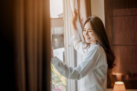 Young woman asia wake up refreshed in the morning and relax in the bedroom on holiday. Asian, asia, relax, alone, technology, lifestyle concept. 스톡 콘텐츠