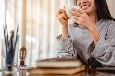 Woman holding a coffee cup work from home wait epidemic situation to improve soon at home. Coronavirus, covid-19, Work from home (WFH), Social distancing, Quarantine, Prevent infection concept.