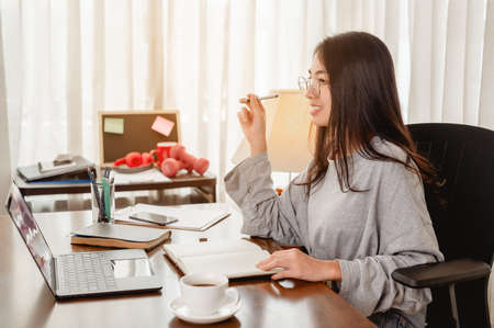 Woman work from home have a coffee cup beside wait epidemic situation to improve soon at home. Coronavirus, covid-19, Work from home (WFH), Social distancing, Quarantine, Prevent infection concept. 스톡 콘텐츠