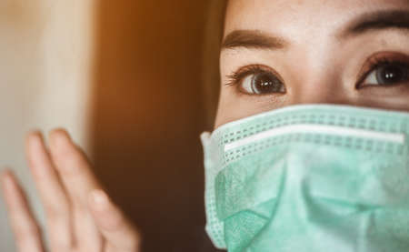 Woman wearing mask protection at the window wait for epidemic situation to improve soon at home. Coronavirus, covid-19, Work from home (WFH), Social distancing, Quarantine, Prevent infection concept. 스톡 콘텐츠
