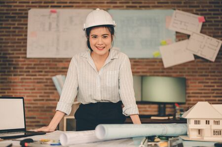 Female architect are holding on blueprint and wear a helmet working engineering or architecture project. Engineer, Engineering, Architecture, Blueprint, Planning, Occupation concept.