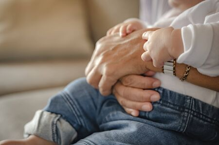 The mother's hand that holds the child on the sofa at home. Family, mother, son, baby, Happy, lifestyle concept. Banco de Imagens