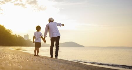 Family, travel, beach, relax, lifestyle, holiday concept. Father and his son who enjoy a picnic and sea bathing at the beach on sunset in holiday.