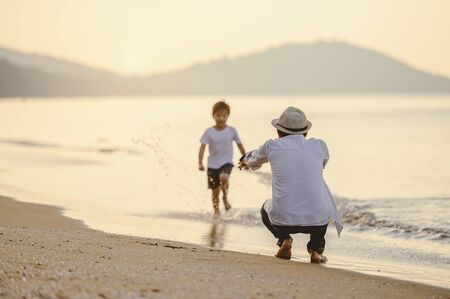 Family, travel, beach, relax, lifestyle, holiday concept. Family who enjoy a picnic. Father is carrying his son at the beach on sunset in holiday.