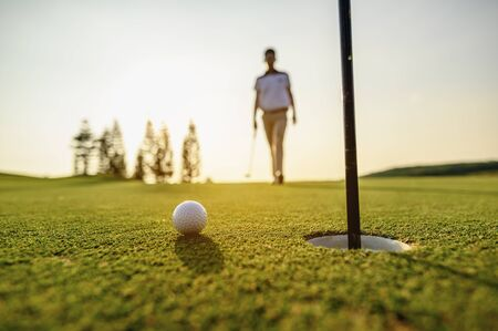 lifestyle, golf, activity, outdoor, sport, golfer concept. Golf balls that are going to be hole by golfers at the green grass golf course at sunset. Stockfoto
