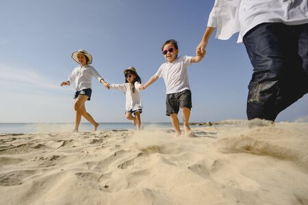 Family who enjoy a picnic. Parents are holding hands their children and walking on the beach at sunset in holiday.