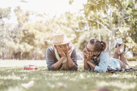 Senior, couples, retirement, insurance, elderly, lifestyle concept. Senior couples sitting and talking on the outdoor lawn in the morning about life insurance plans with a happy retirement concept.