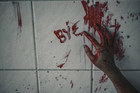 Horror woman write a message requesting help with blood in hand, Halloween murder concept. 스톡 콘텐츠