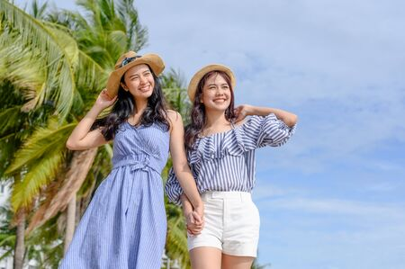Two happy woman holding straw hat at the beach with coconut trees