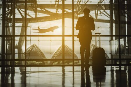 Silhouettes of Businessman and His suitcase Waiting for the planeat the airport. ravel and business airport concept.